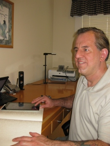 Larry Lewis, author of iOS Success, sitting at his desk with a copy of the book and an iPad