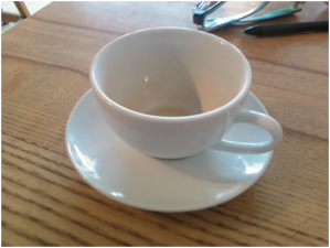 White cup and saucer on a wooden table