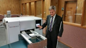 Steve Booth standing next to copy machine at his office