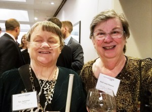 Photo of Sue and Ruth Ann Hansen wearing nametags and smiling at the camera